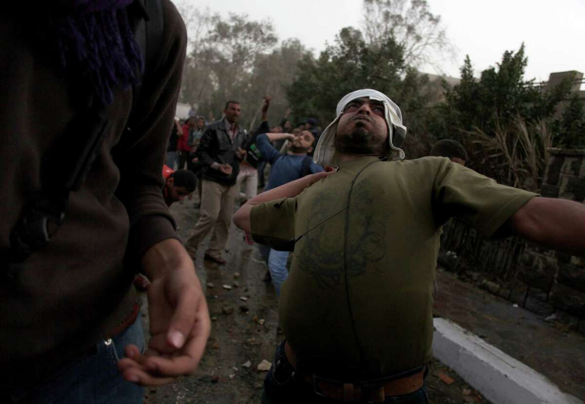 An Egyptian protester throws a stone during clashes between supporters and opponents and supporters of Egypt?'s powerful Muslim Brotherhood near the Islamist group?'s Cairo, Egypt headquarters Friday, March 22, 2013. (AP Photo/Khalil Hamra)