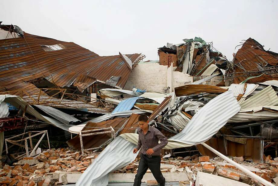 This picture taken on March 21, 2013 shows a man walking in a damaged factory after a serious storm and heavy wind hit the area in Dongguan, south China's Guangdong province.  South China was warned on March 22 to prepare for more heavy rain and hailstorms, as five provinces continue to repair damage caused by severe weather which resulted in the deaths of at least 24 people.AFP PHOTOSTR/AFP/Getty Images Photo: Str, AFP/Getty Images