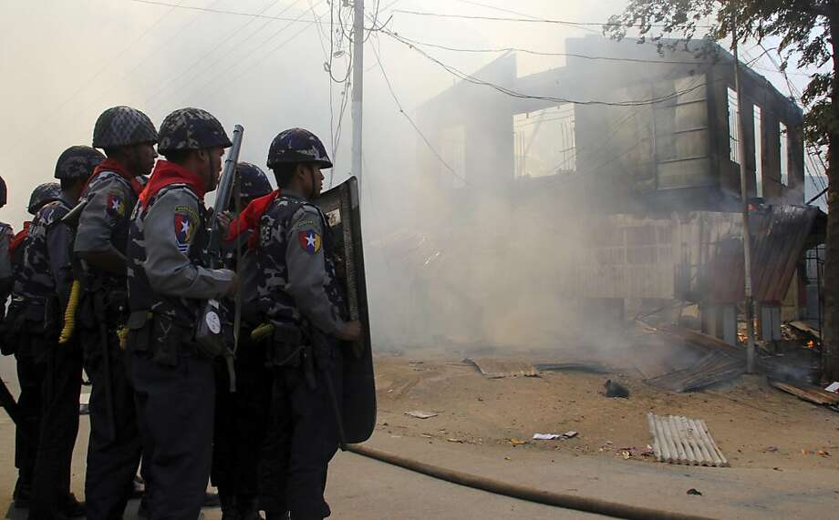 In this Thursday, March 21, 2013 photo, armed Myanmar police oficers provide security around a smoldering building following ethnic unrest between Buddhists and Muslims in Meikhtila, Mandalay division, about 550 kilometers (340 miles) north of Yangon, Myanmar. Burning fires from two days of Buddhist-Muslim violence that killed at least 20 people smoldered across a central Myanmar town Friday as residents cowered indoors amid growing fears the country's latest bout of sectarian bloodshed could spread. The government's struggle to contain the unrest in Meikhtila is proving another major challenge President Thein Sein's reformist administration as it attempts to chart a path to democracy after nearly half a century of military rule that once crushed all dissent. (AP Photo) Photo: Associated Press
