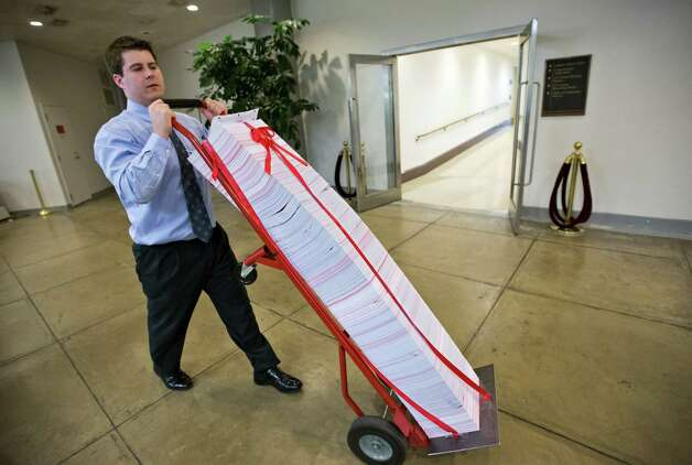 "A Senate aide delivers a stack of documents bound in red tape being used as a prop during debate on the budget in the Senate, at the Capitol in Washington, Friday, March 22, 2013. The paperwork was described as the federal regulations dealing with the Affordable Care Act, often called ""Obamacare."" (AP Photo/J. Scott Applewhite) Photo: J. Scott Applewhite"