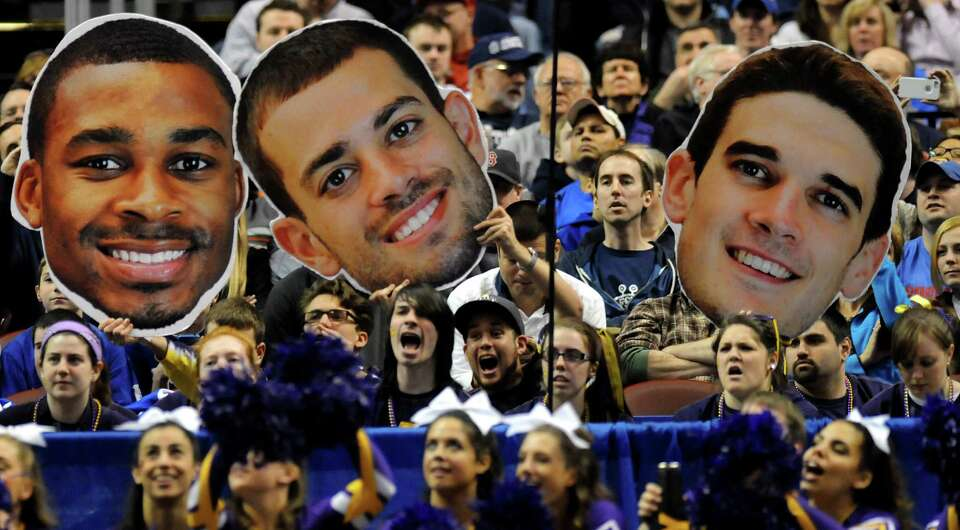 UAlbany fans hold up larger-than-life cutouts of Mike Black, left, Jacob Iati, center, and John Puk