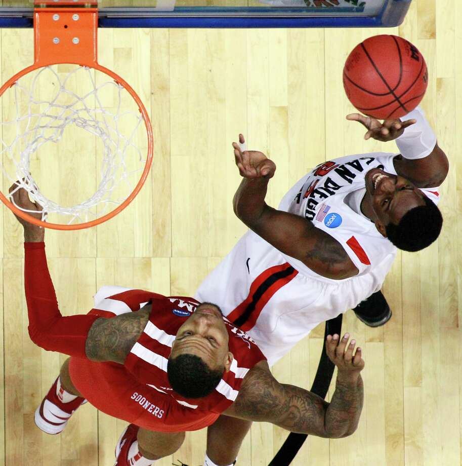 San Diego State's Deshawn Stephens, right, shoots as Oklahoma's Romero Osby defends during the first half of a second-round game of the NCAA college basketball tournament on Friday, March 22, 2013, in Philadelphia. (AP Photo/Matt Rourke) Photo: Matt Rourke, Associated Press / AP