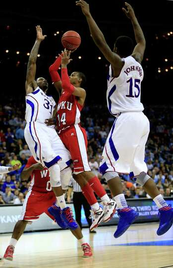 Jamal Crook #14 of the Western Kentucky Hilltoppers shoots against Jamari Traylor #31 and Elijah Joh