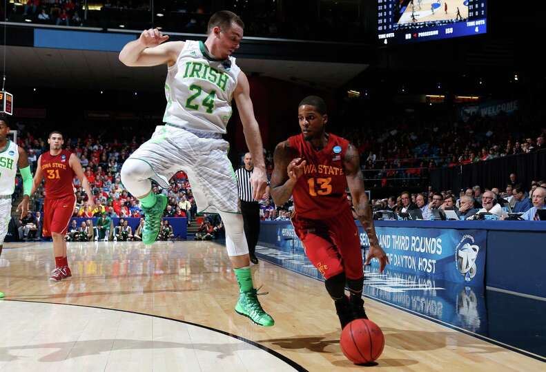 Korie Lucious #13 of the Iowa State Cyclones dribbles against Pat Connaughton #24 of the Notre Dame