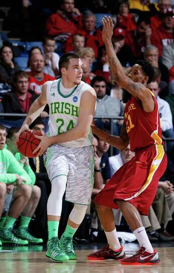 Pat Connaughton #24 of the Notre Dame Fighting Irish handles the ball against Will Clyburn #21 of th