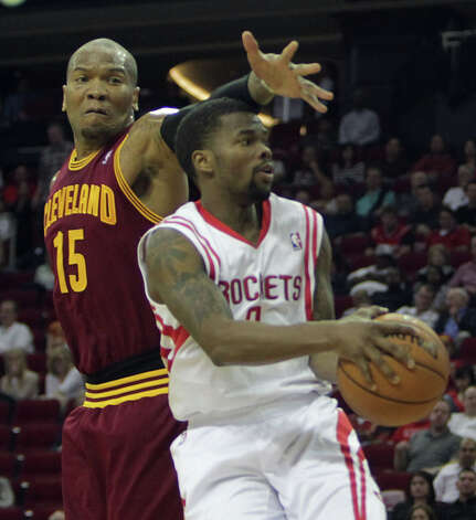 Aaron Brooks of the Rockets drives against Marreese Speights of the Cavs. Photo: James Nielsen / © 2013 Houston Chronicle