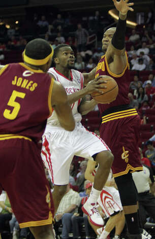 Kevin Jones and Marreese Speights of the Cavaliers defend Aaron Brooks of the Rockets. Photo: James Nielsen / © 2013 Houston Chronicle