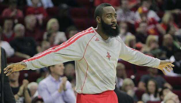 Rockets guard James Harden reaches out to teammates during the first quarter. Photo: James Nielsen / © 2013 Houston Chronicle