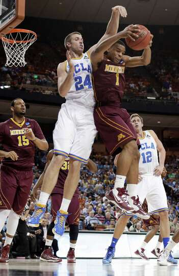 Minnesota's Andre Hollins (1) pulls down a rebound in front of UCLA's Travis Wear (24) during the fi
