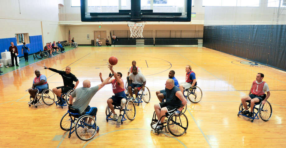 Players stretch for a rebound during a basketball game as part of the Warrior Adaptive Sports Camp for the Air Force wounded. Photo: Photos By Robin Jerstad / For The San Antonio Express-News