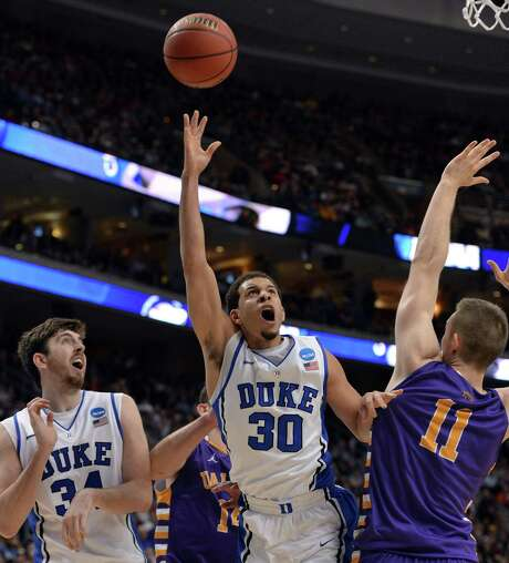 Duke's Seth Curry (30) shoots over Albany's Luke Devlin in the second half. Curry scored 26 points as the Blue Devils advanced with a 73-61 victory. Photo: Chuck Liddy / McClatchy-Tribune News Service