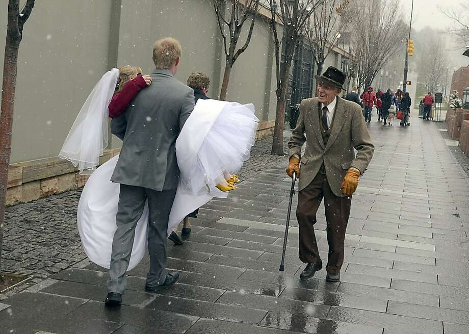 "After a wedding photo shoot in front of the Salt Lake Temple, groom Evan Call carries his bride Samantha to help keep her dress from getting muddy, Friday, March 22, 2013 in Salt Lake City. ""Her feet were freezing too,"" said Call as the newlyweds headed back the temple to join their wedding party. (AP Photo/The Spokesman-Review, Colin Mulvany)  Photo: Colin Mulvany, Associated Press"