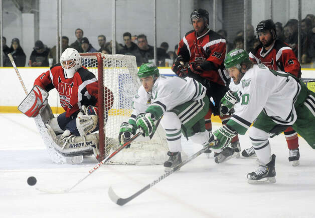 Danbury players fight for the puck during the Danbury Whalers' 6-3 win over the Dayton Demons in the Commisioner's Cup finals at Danbury Arena in Danbury, Conn. on Friday, March 22, 2013. Photo: Tyler Sizemore / The News-Times