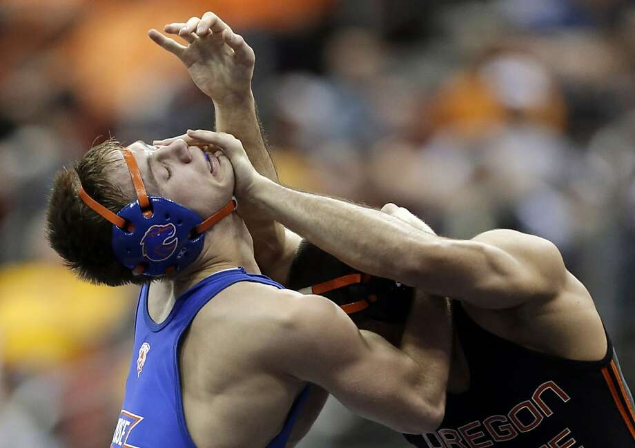 Boise State's Jason Chamberlain, left, fights off Oregon State's Scott Sakaguchi during their 149-pound quarterfinal round match at the NCAA Division I wrestling championships, Friday, March 22, 2013, in Des Moines, Iowa. (AP Photo/Charlie Neibergall) Photo: Charlie Neibergall, Associated Press