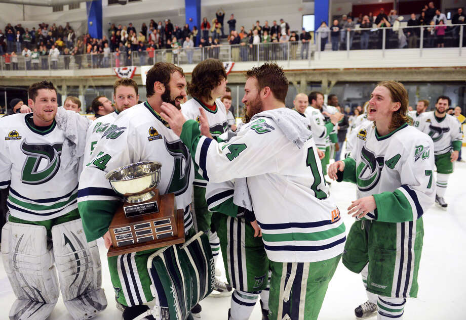 Danbury goalie Mike Brown holds the MVP trophy and is congratulated by teammates after the Danbury Whalers' 6-3 win over the Dayton Demons in the Commisioner's Cup finals at Danbury Arena in Danbury, Conn. on Friday, March 22, 2013. Photo: Tyler Sizemore / The News-Times