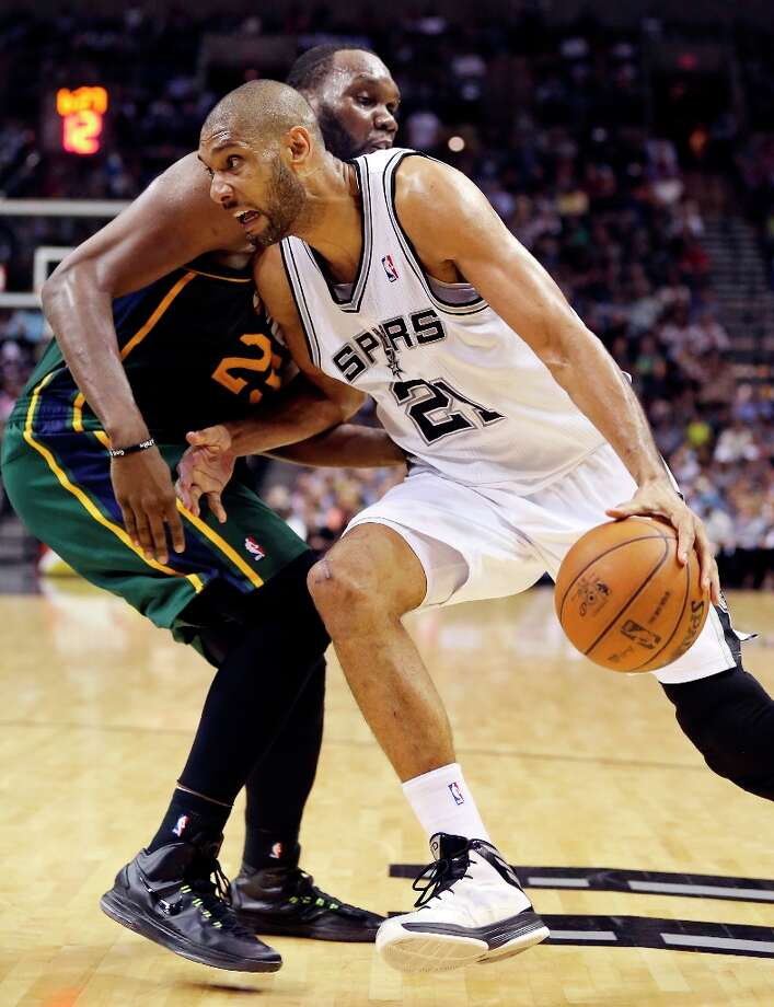 The Spurs' Tim Duncan looks for room around Utah Jazz's Al Jefferson during second half action Friday, March 22, 2013 at the AT&T Center. The Spurs won 104-97 in overtime. Photo: Edward A. Ornelas, San Antonio Express-News / © 2013 San Antonio Express-News