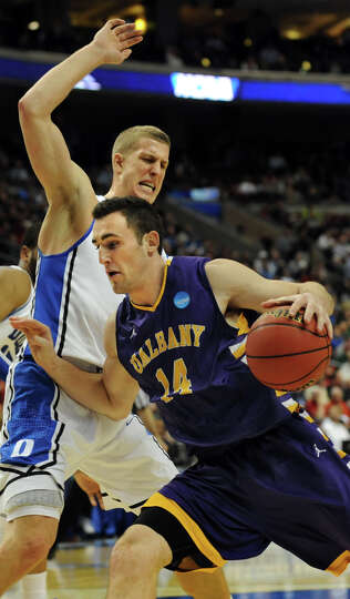 UAlbany's Sam Rowley, right, drives past Duke's Mason Plumlee during their second round NCAA Tournam