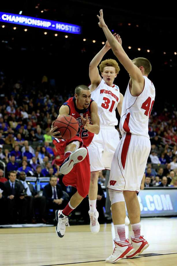 KANSAS CITY, MO - MARCH 22: Marshall Henderson #22 of the Ole Miss Rebels shoots against Mike Bruesewitz #31 and Jared Berggren #40 of the Wisconsin Badgers in the second half during the second round of the 2013 NCAA Men's Basketball Tournament at the Sprint Center on March 22, 2013 in Kansas City, Missouri.  (Photo by Jamie Squire/Getty Images) Photo: Jamie Squire