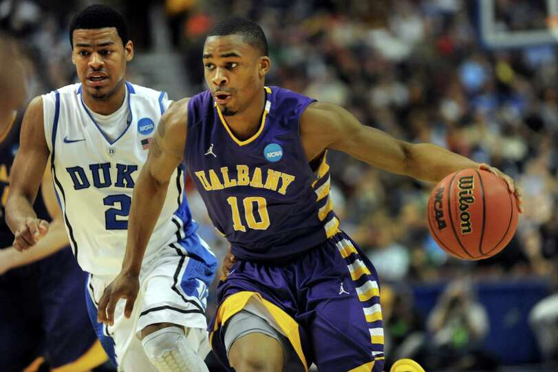 UAlbany's Mike Black, right, drives up court as Duke's Quinn Cook defends during their second round