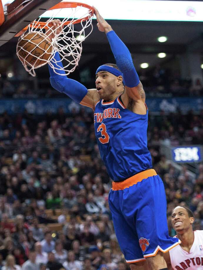 New York Knicks forward Kenyon Martin dunks the ball past Toronto Raptors forward DeMar DeRozan, right, during second half NBA basketball action in Toronto on Friday, March 22, 2013. (AP Photo/The Canadian Press, Nathan Denette) Photo: Nathan Denette