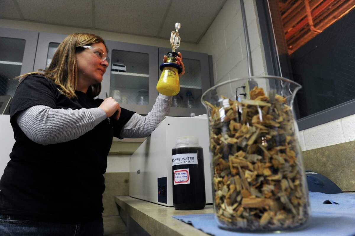 In this photo taken Feb. 4, 2012, Process Manager Amanda Huber looks at the CO2 coming out of the flasks filled with 93% corn mash and 7% cellulosic sugar in Windsor, Colo. The cellulosic sugar was extracted from beetle kill wood from Colorado. Huber is working on a lab scale fermentation trial of cellulosic feed stock, such as beetle kill wood, to create a new source for making ethanol other than corn. Colorado ethanol producer Front Range Energy will be among the first in the nation to start using crop residue and other biomass in place of corn for a portion of its ethanol production. The company is in the process of testing Colorado beetle kill trees as a source of alternative biomass to corn. (AP Photo/The Denver Post, Helen H. Richardson)
