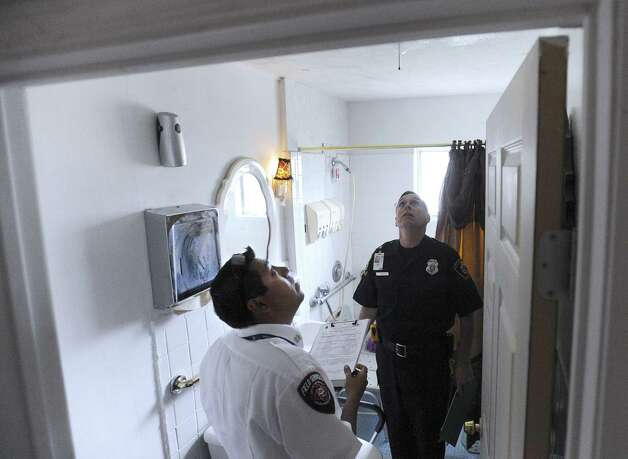 Inspectors Jose Ramirez (foreground) and Andrew Smart examine a bathroom in a boarding home on Seabrook Drive. Photo: Billy Calzada / San Antonio Express-News