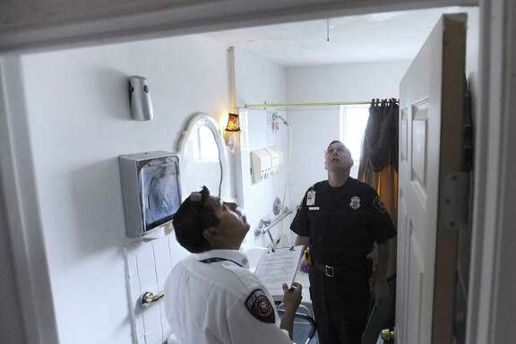 Inspectors Jose Ramirez (foreground) and Andrew Smart examine a bathroom in a boarding home on Seabrook Drive.