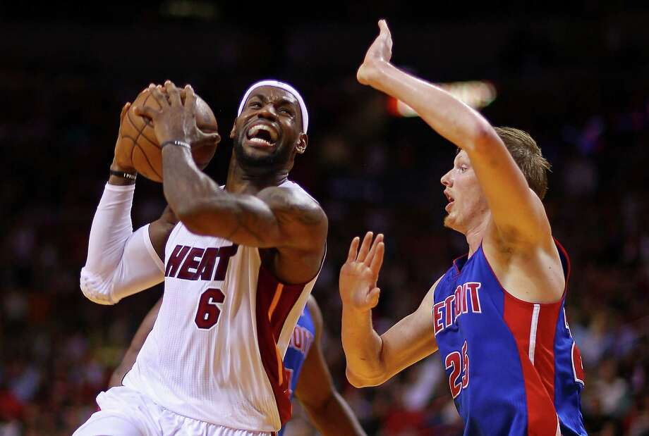 Heat forward LeBron James posts up Detroit's Kyle Singler en route to scoring a game-high 29 points. Photo: Mike Ehrmann, Staff / 2013 Getty Images