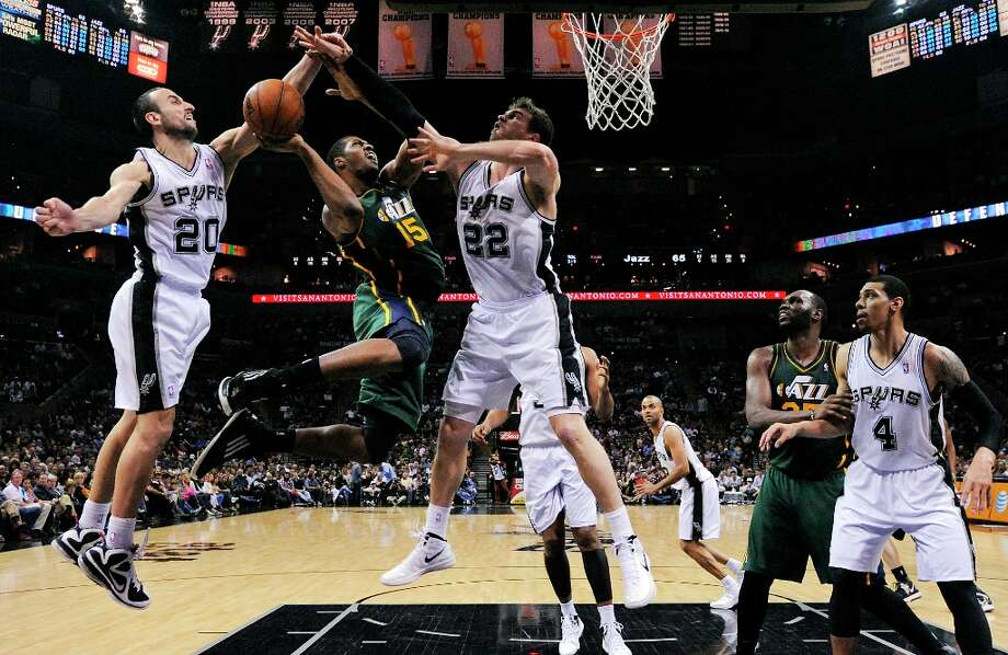 The Spurs' Manu Ginobili (from left) and Tiago Splitter defend Utah Jazz's Derrick Favors during second half action as Utah Jazz's Al Jefferson and Spurs' Danny Green look on Friday, March 22, 2013 at the AT&T Center. The Spurs won 104-97 in overtime. Photo: Edward A. Ornelas, San Antonio Express-News / © 2013 San Antonio Express-News