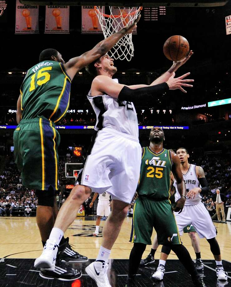 The Spurs' Tiago Splitter shoots around Utah Jazz's Derrick Favors during first half action Friday, March 22, 2013 at the AT&T Center. The Spurs won 104-97 in overtime. Photo: Edward A. Ornelas, San Antonio Express-News / © 2013 San Antonio Express-News