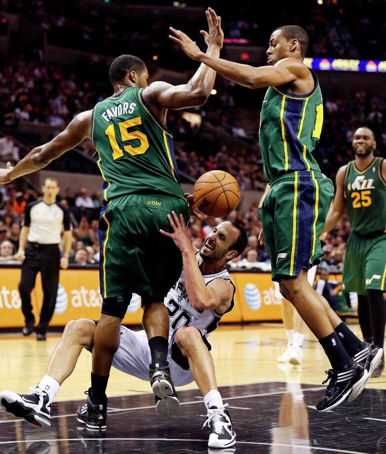 The Spurs' Manu Ginobili slips while driving to the basket between Utah Jazz's Derrick Favors (left) and Alec Burks during second action Friday, March 22, 2013 at the AT&T Center. The Spurs won 104-97 in overtime. Photo: Edward A. Ornelas, San Antonio Express-News / © 2013 San Antonio Express-News