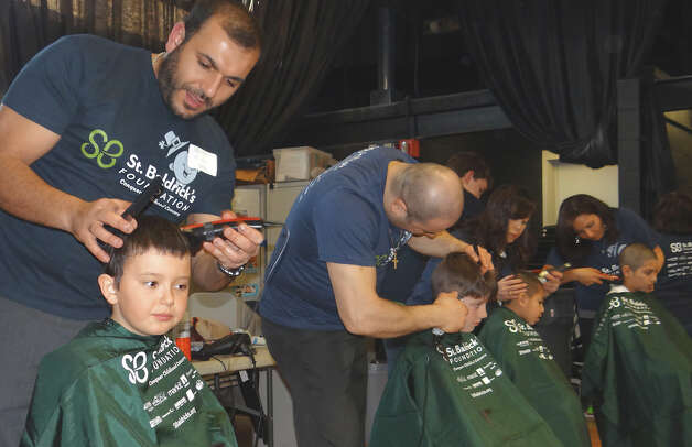 Salon Isa staff work in assembly line fashion to shave heads Friday at the St. Baldrick's Team Teddy fundraiser at Osborn Hill School.  FAIRFIELD CITIZEN, CT 3/22/13 Photo: Mike Lauterborn / Fairfield Citizen contributed