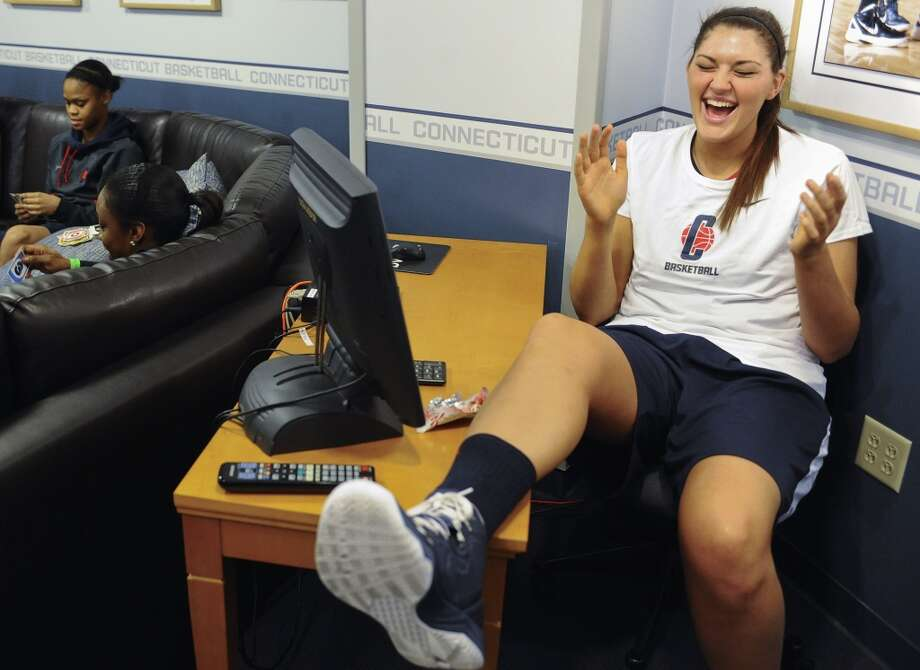 Connecticut's Stefanie Dolson, right, laughs as her teammates play cards in their locker room before practice for a first-round game in the women's NCAA college basketball tournament in Storrs, Conn., Friday, March 22, 2013. Connecticut will play Idaho on Saturday. (AP Photo/Jessica Hill)
