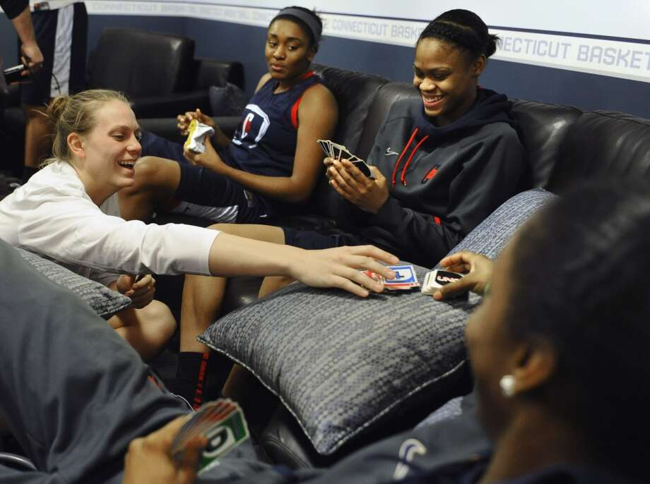 Connecticut's Heather Buck, left, makes a move in a game of Uno with teammates, Moriah Jefferson, second from right, and Brianna Banks, right, as Morgan Tuck, second from left, looks on before practice for a first-round game in the women's NCAA college basketball tournament in Storrs, Conn., Friday, March 22, 2013. Connecticut will play Idaho on Saturday. (AP Photo/Jessica Hill)