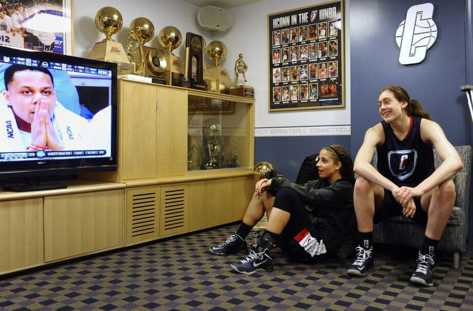 Connecticut's Caroline Doty, left, and Breanna Stewart, right, watch men's college basketball on television in their locker room before practice for a first-round game in the women's NCAA college basketball tournament in Storrs, Conn., Friday, March 22, 2013. Connecticut will play Idaho on Saturday. (AP Photo/Jessica Hill)