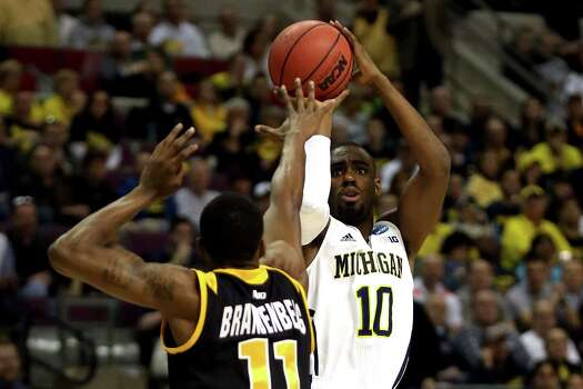 Tim Hardaway Jr. #10 of the Michigan Wolverines attempts a shot in the first half against Rob Brandenberg #11 of the Virginia Commonwealth Rams. Photo: Jonathan Daniel, Getty Images / 2013 Getty Images