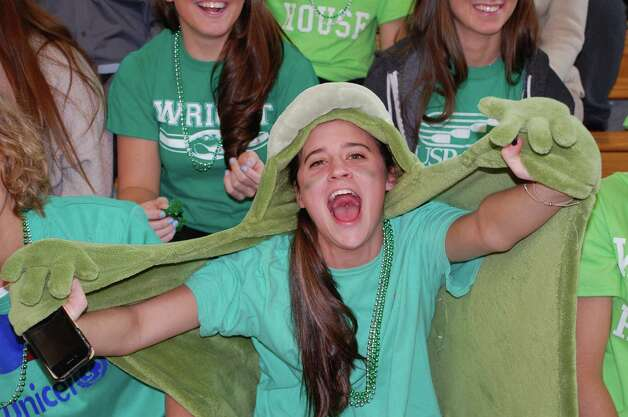 "Lily Powers, 17, gives it up for the green Wright House Alligators at Friday's Battle of the Houses at Fairfield Ludlowe High. ""I like being in Wright House, because we're like the underdogs, but we're gonna win this year, my senior year,"" she said.  FAIRFIELD CITIZEN, CT 3/22/13 Photo: Jarret Liotta / Fairfield Citizen contributed"
