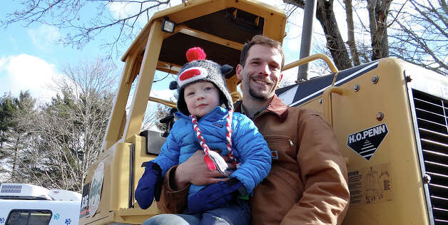 James Brys of Geiger's Nursery with Graham Zorumski, 3, of New Canaan, atop a bulldozer Saturday at the Touch-A-Truck event.  WESTPORT NEWS, CT 3/23/13 Photo: Mike Lauterborn / Westport News contributed