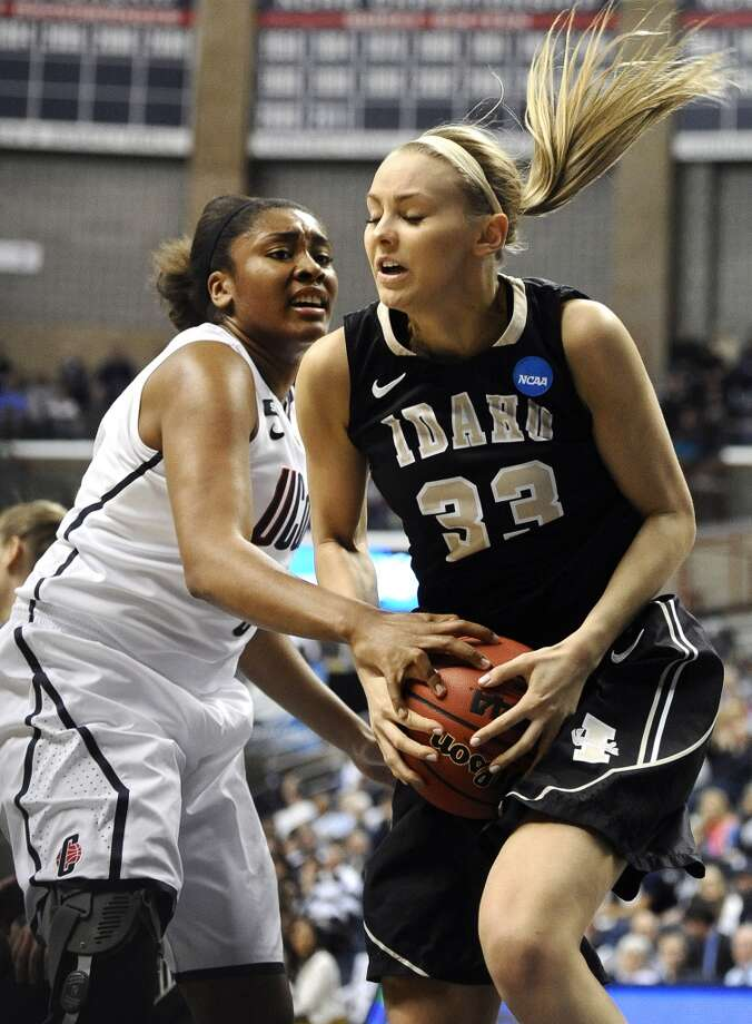 Idaho's Alyssa Charlston, right, hangs onto a rebound against Connecticut's Morgan Tuck in the first half of a first-round game in the women's NCAA college basketball tournament in Storrs, Conn., Saturday, March 23, 2013. (AP Photo/Jessica Hill)
