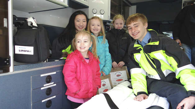Westport EMS volunteers Judy Feng and Mark Kaminsky give an ambulance tour to Bryn, Emma and Cate Morris of Westport at the Touch-A-Truck event on Saturday.    WESTPORT NEWS, CT 3/23/13 Photo: Mike Lauterborn / Westport News contributed