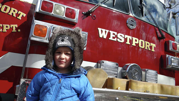 Will Kiefer, 3, of Westport stands beside Westport Fire Department's Engine 8 at Touch-A-Truck on Saturday at Coleytown Elementary School.  WESTPORT NEWS, CT 3/23/13 Photo: Mike Lauterborn / Westport News contributed