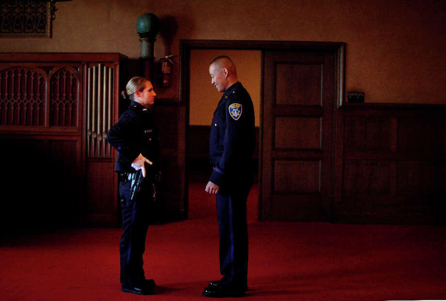 Amerra Kesterson (l to r) practices the Chief's inspection of the gun with Ken Bui as the Oakland Police Department's 166th Basic Academy prepares for Graduation Exercise at the Scottish Rite Center on Friday, March 22, 2013 in Oakland, Calif. Photo: Lea Suzuki, The Chronicle / ONLINE_YES