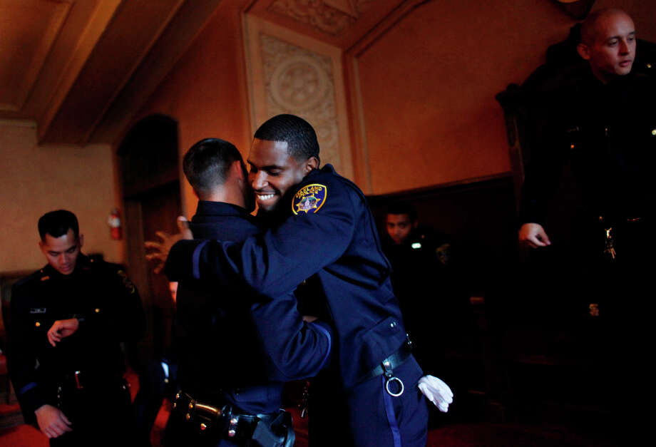 Cedric Remo hugs a fellow classmate of the Oakland Police Department's 166th Basic Academy as they prepare for Graduation Exercise at the Scottish Rite Center on Friday, March 22, 2013 in Oakland, Calif. Photo: Lea Suzuki, The Chronicle / ONLINE_YES