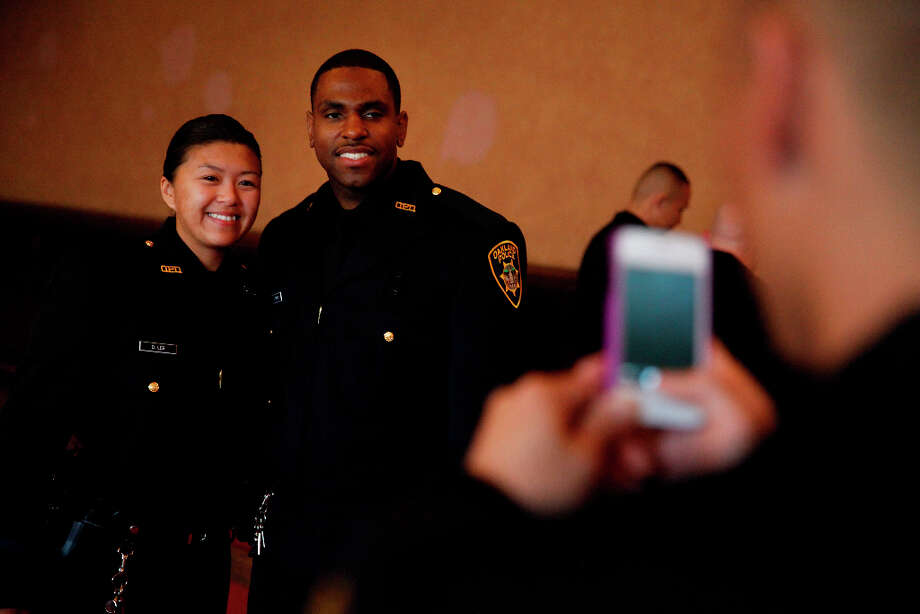 Cedric Remo (right) and Dana Lee (left) pose for a photo together before the Oakland Police Department's 166th Basic Academy Graduation Exercise at the Scottish Rite Center on Friday, March 22, 2013 in Oakland, Calif. Photo: Lea Suzuki, The Chronicle / ONLINE_YES