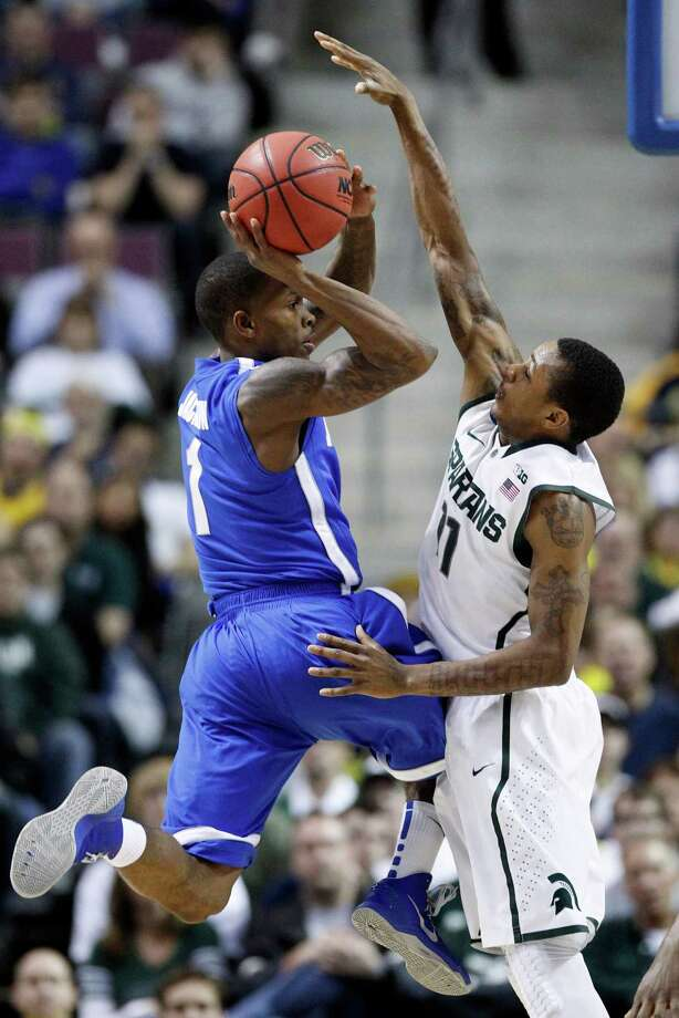 Memphis guard Joe Jackson (1) is forced to pass the ball against the defense from Michigan State guard Keith Appling (11) in the first half of a third-round game of the NCAA college basketball tournament Saturday, March 23, 2013, in Auburn Hills, Mich. (AP Photo/Duane Burleson) Photo: Duane Burleson, Associated Press / FR38952 AP