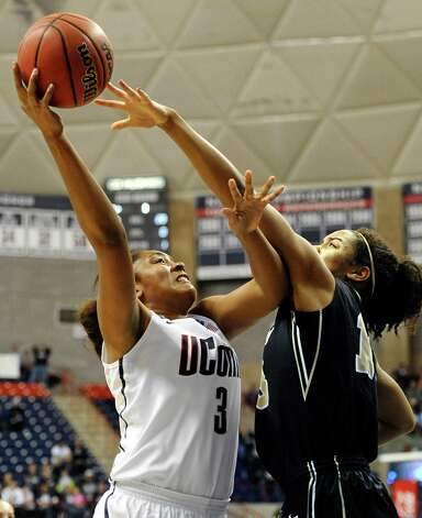 Connecticut's Morgan Tuck, left, goes up for a basket while guarded by Idaho's Ali Forde, right, during the first half of a first-round game in the women's NCAA college basketball tournament in Storrs, Conn., Saturday, March 23, 2013. Connecticut won 105-37. (AP Photo/Jessica Hill) Photo: Jessica Hill, Associated Press / FR125654 AP