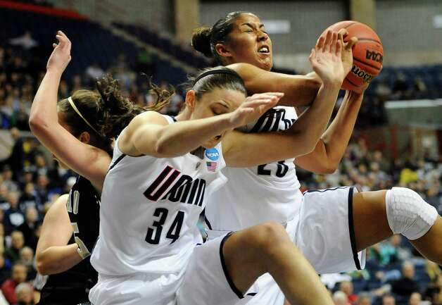Connecticut's Kaleena Mosqueda-Lewis, right, pulls down a rebound against Idaho's Connie Ballestero, left, as Connecticut's Kelly Faris (34) defends in the second half of a first-round game in the women's NCAA college basketball tournament in Storrs, Conn., Saturday, March 23, 2013. Connecticut won 105-37. (AP Photo/Jessica Hill) Photo: Jessica Hill, Associated Press / FR125654 AP