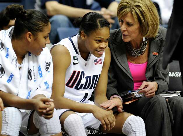 Connecticut's Moriah Jefferson, center, smiles as associate head coach Chris Dailey, right, speaks to her, and teammate Kaleena Mosqueda-Lewis, left, sits near in the second half of a first-round game in the women's NCAA college basketball tournament against Idaho in Storrs, Conn., Saturday, March 23, 2013. Jefferson scored 16 points as Connecticut won 105-37. (AP Photo/Jessica Hill) Photo: Jessica Hill, Associated Press / FR125654 AP