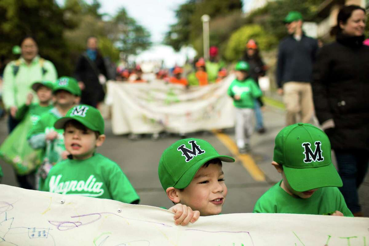Children, holding team sponsor signs, march in the annual Magnolia Little League parade.