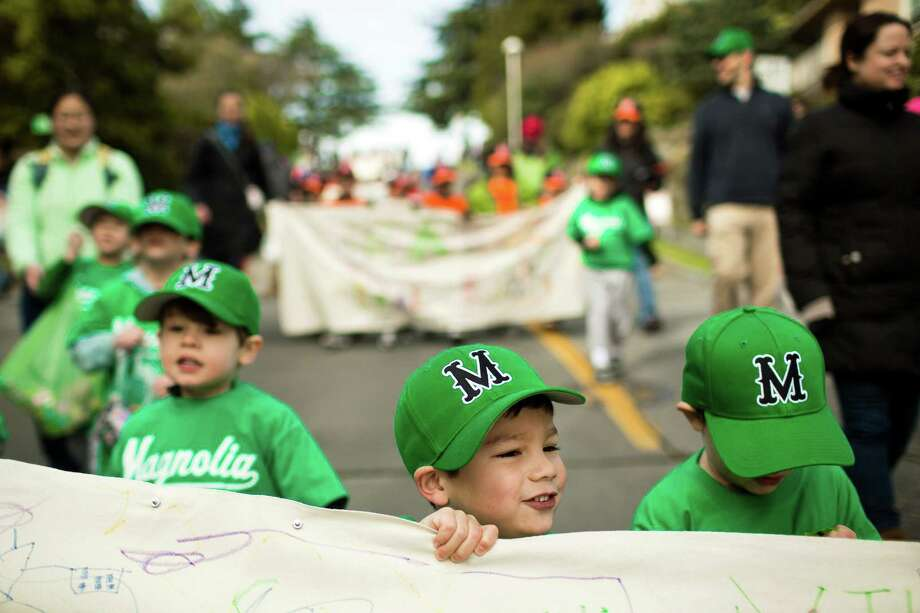 Children, holding team sponsor signs, march in the annual Magnolia Little League parade. Photo: JORDAN STEAD / SEATTLEPI.COM
